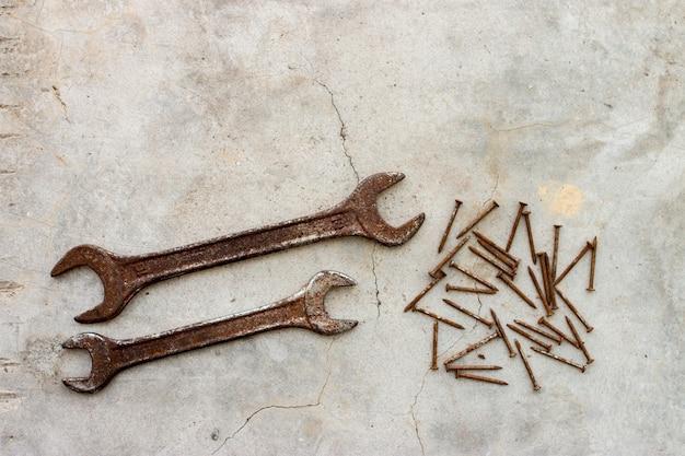 Ржавый гаечный ключ и гвозди на бетонном полу
