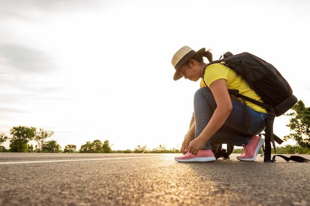 太陽の黄金色の光で高速道路でスニーカーを結ぶ女性観光客