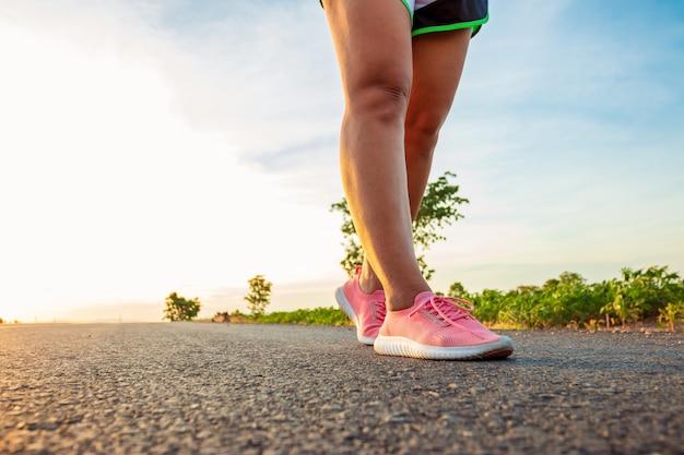 日没の丘の中腹の道に沿って女性が走って運動しています。