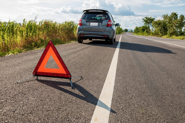 道路上の緊急停止標識と壊れた車