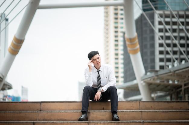ビジネスの男性が階段に座っていると彼の仕事について考えています
