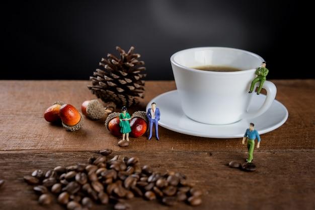 一杯の熱いブラックコーヒーが木製のテーブルの上にあり、コーヒー豆と小さなフィギュアモデルで飾られています。