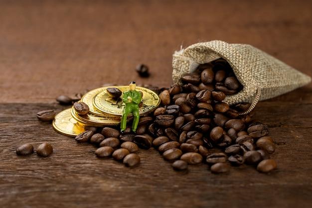木製のバケツで満たされたコーヒー豆、いくつかはテーブルと布の袋に広げられます。黄金のコインとビジネスの男性モデルで飾る。
