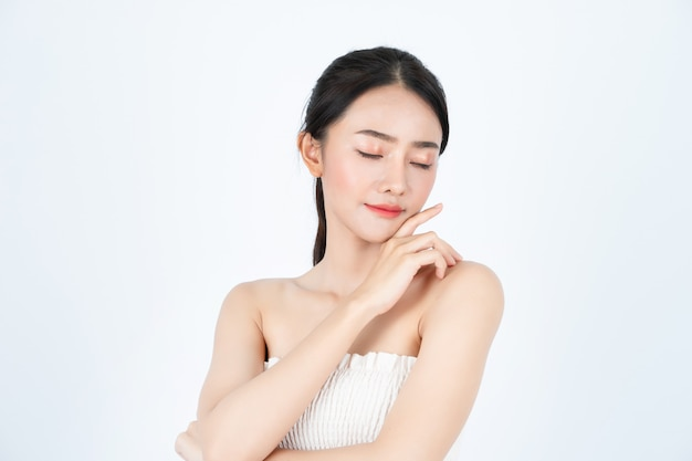 白いアンダーシャツの若いアジアの美しい女性は、健康で明るい肌をしています。