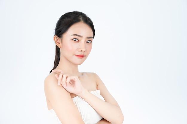 白いアンダーシャツのアジアの美しい女性は、明るく健康的な肌を示しています。