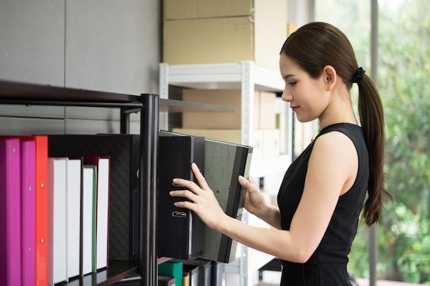 マネージャーが事務所の棚の隣に立っています。彼女は黒のスーツを着ていてフォルダーを持っています。