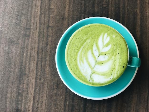 白いテーブルに緑の抹茶ラテコーヒーのカップ。上面図。