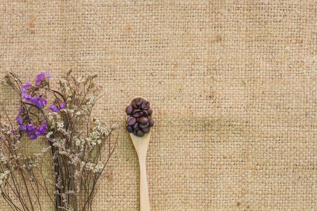 袋の背景に乾燥した花の袋に入ったコーヒー豆。