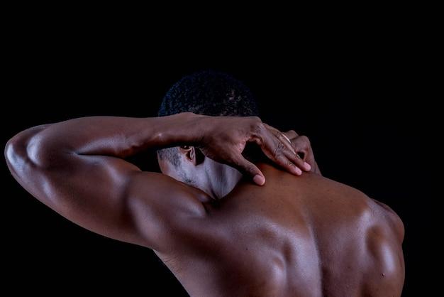 痛みの首を運動する健康的な若いアフリカの男。黒い背景のボディービルダートレーニング