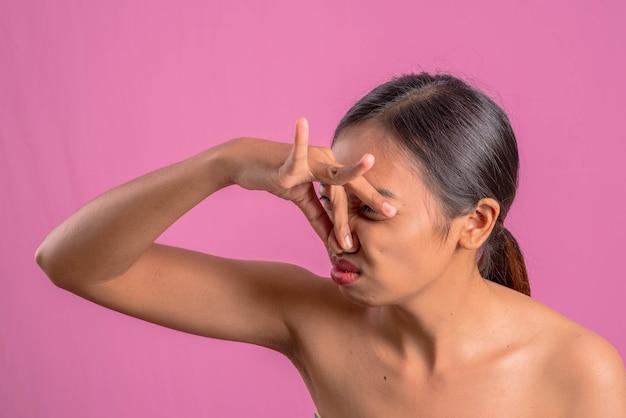健康な若いアジア人のラテンの女性。女性は、ピンクの背景を覆っています。