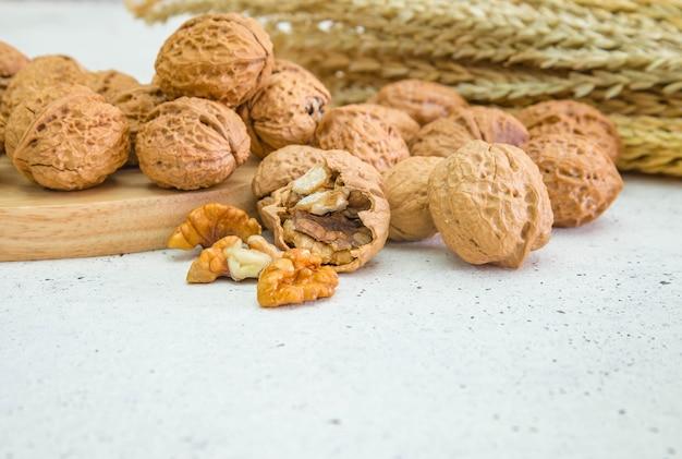素朴な古い木製のテーブル上のウォールナットの穀物と全体のクルミ