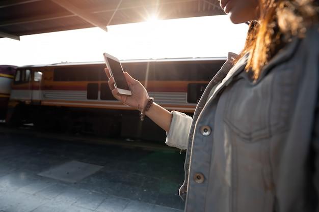アジアの女性が電車で旅行のためのスマートフォンを使用して