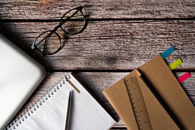 メガネと木製のテーブル上のラップトップと文房具。