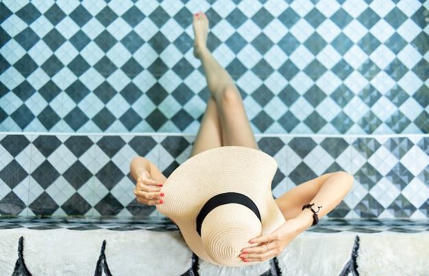 麦わら帽子をかぶってプールでリラックスした女性。