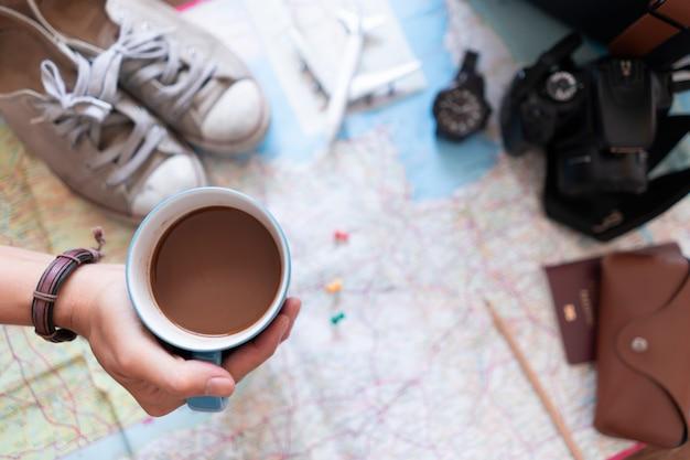 Рука держать кофе и планирование поездки
