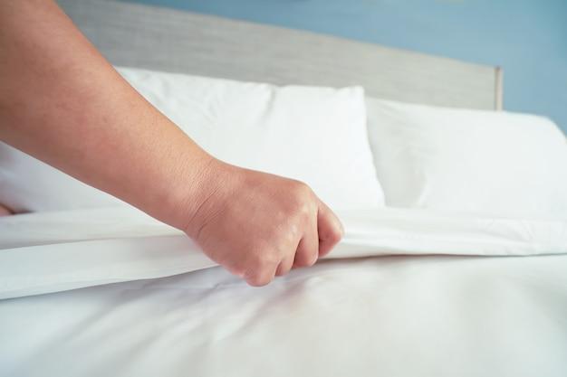 女性の手が部屋のホテルで白いシーツを設定