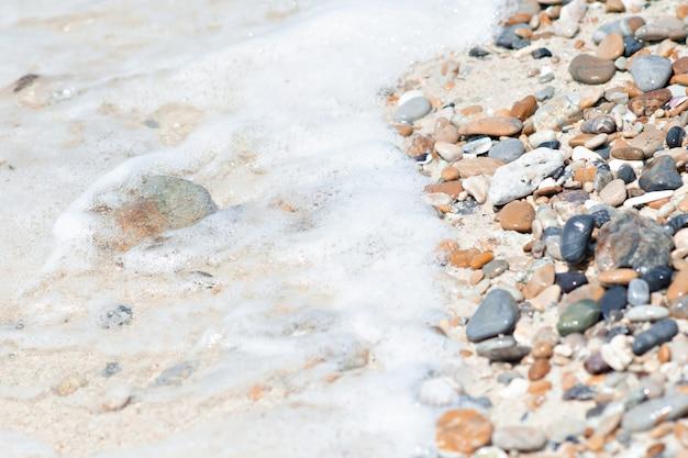 海の背景で浜辺の石