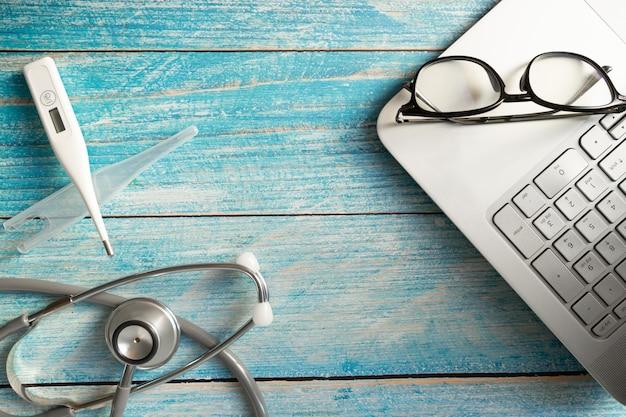 テーブルの上のラップトップ上の聴診器。医師と技術のためのオブジェクト