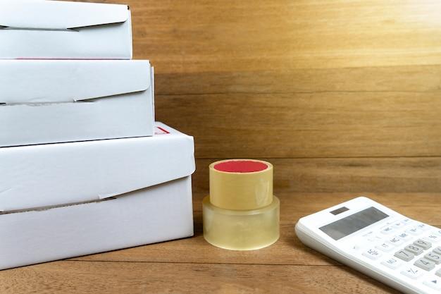 木製のテーブル上の電卓と積み重ねられた段ボール箱。