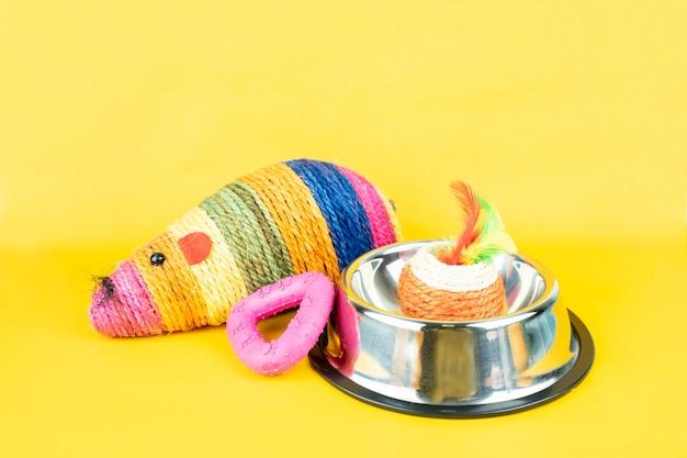 色の背景上のステンレスボウルと猫のおもちゃ。ペットアクセサリーコンセプト