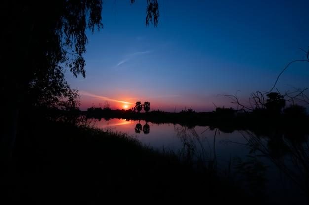 Силуэт деревьев с озером на фоне заката