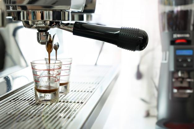 カフェでコーヒーメーカーとブラックホットコーヒー