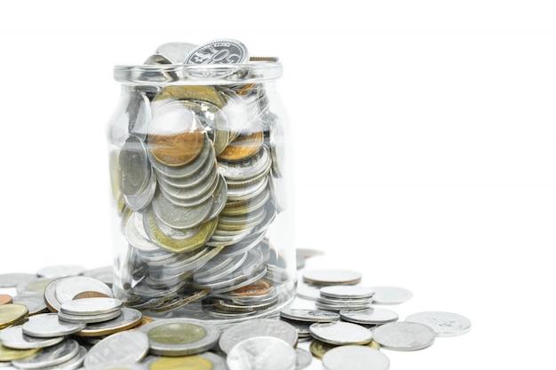 分離された白のコピースペースとガラスの瓶にコイン。お金の概念を保存