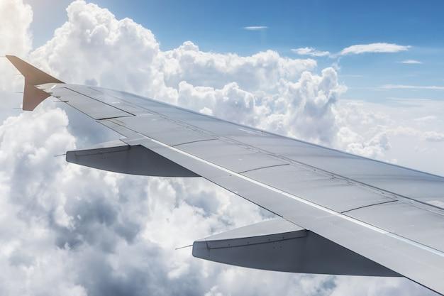 飛行機の窓の外を見てください。空と曇り空に翼を内側から見る
