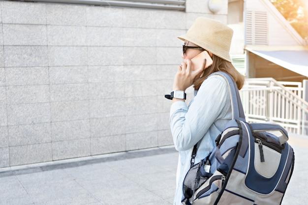 バックパックを持つ女性旅行者は、スマートフォンを使用します。旅行のコンセプト