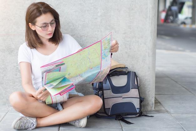 アジアの女性が座って、市内旅行の地図を持っています。