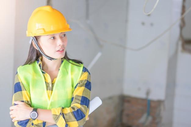Женщины инжиниринг носят желтый шлем и работают на стройке