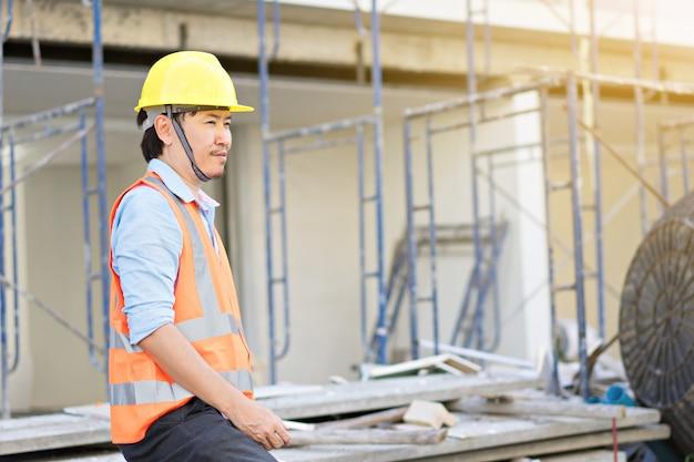 Мужской инженер носить желтый шлем и работает на строительной площадке