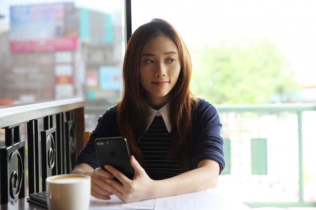 スマートフォンとコーヒーを持つ若いビジネス女性