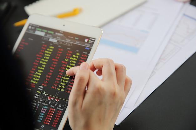 Женская рука, торгующая онлайн на планшете с деловой бумагой и кофе