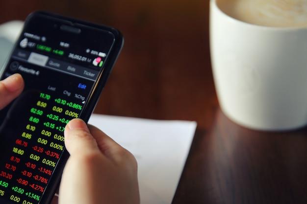 Торгует онлайн на смартфоне с деловой женщиной рукой