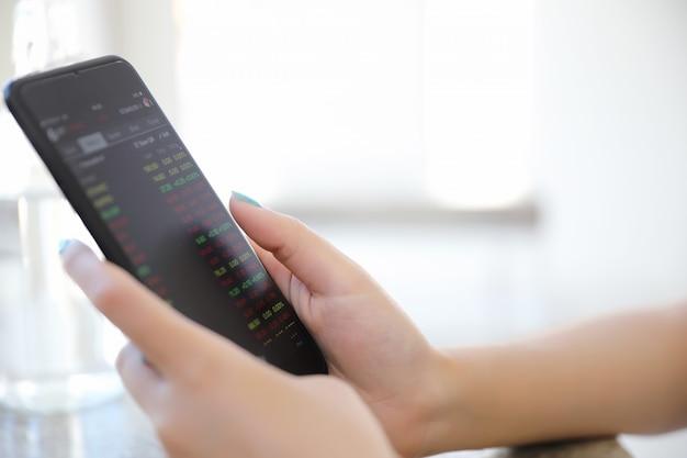 コーヒーショップビジネスコンセプトで株式やデータを取引するスマートフォンを持つ女性の手にクローズアップ
