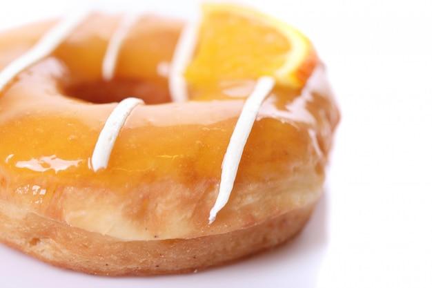 白で隔離されるオレンジドーナツ