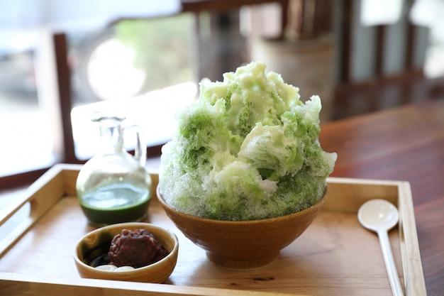 日本のカフェで木製のテーブルに美味しい日本の甘いかき氷緑茶
