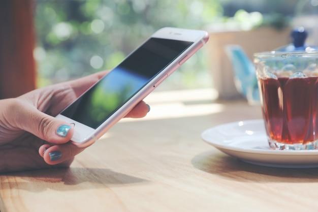 スマートフォン技術の概念を保持している女性の手に近づく