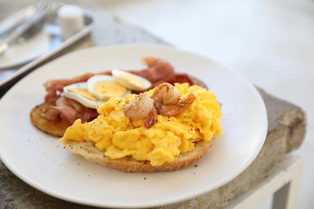 スクランブルエッグ、フライドポテトベーコン、エビの朝食