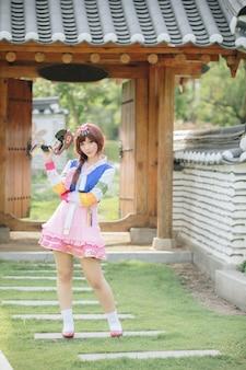 Портрет ханбок костюм молодой женщины глядя и улыбаться в корейском парке
