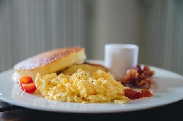 フィルムのヴィンテージスタイルのパンケーキとベーコンの朝食フードでの卵のスクランブル