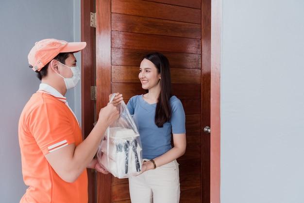 Азиатские мужчины несут товары в оранжевых рубашках.