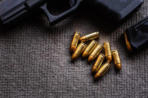 Пули и пистолет на столе из черного бархата