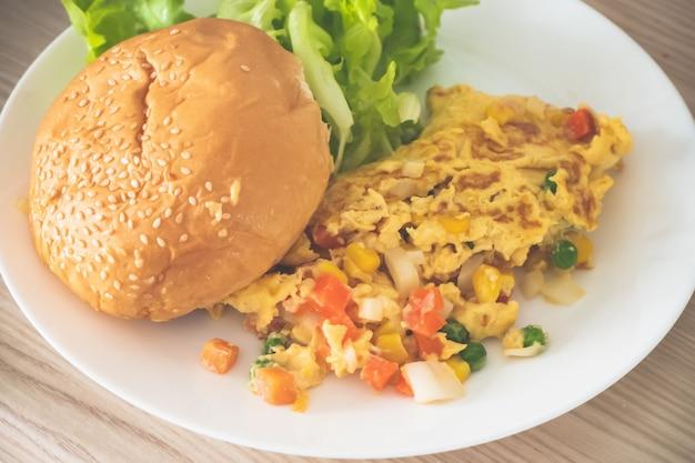 ハンバーガーのパンと白いプレートに野菜のオムレツ