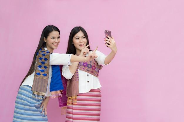 伝統的なタイのドレスでアジア人の若い女の子とセルフを作るスマートフォンを見て
