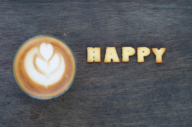 Чашка латте-искусства и алфавит «счастливый» из хлеба
