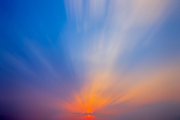フィールドや草原の自然の夕日の日の出。明るく劇的な空と暗い地面。風光明媚なカラフルな空の下で田舎の風景