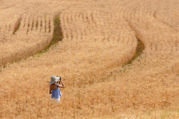 麦畑でカメラ撮影を楽しむ美しい女性