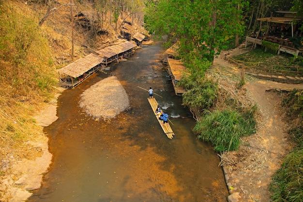 メーワン地区チェンマイタイの観光客のためのツアーとして緑の熱帯風景の中で竹ラフティング